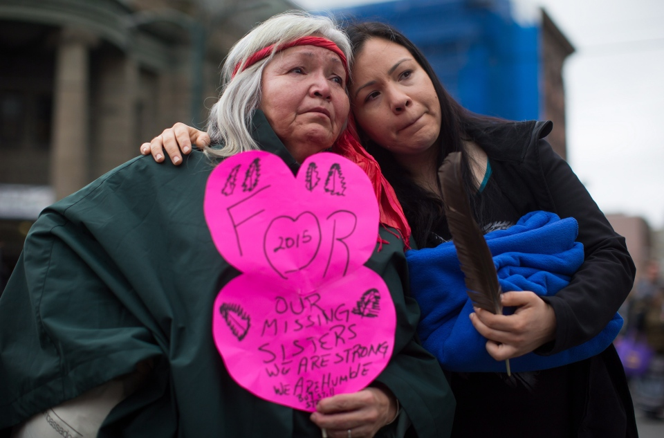 Janet Pete, left, and her niece Genevier Sullivan comfort each other during the 25th annual Women's Memorial March in the Downtown Eastside of Vancouver, B.C., on Saturday February 14, 2015.  (Darryl Dyck / THE CANADIAN PRESS)