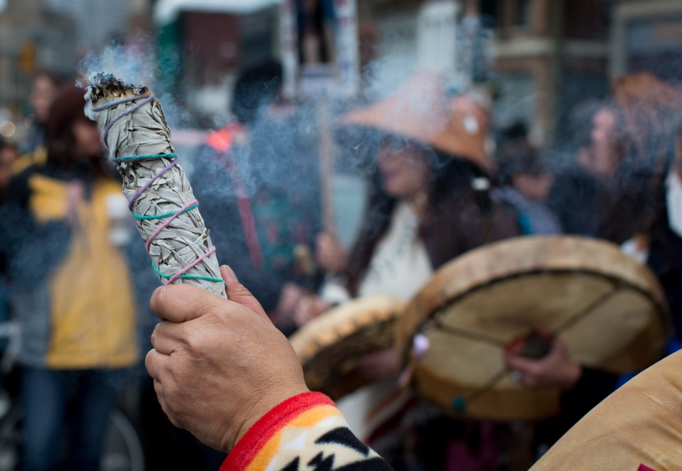 Medicine is burned as women drum during the 25th annual Women's Memorial March in the Downtown Eastside of Vancouver, B.C., on Saturday February 14, 2015.  (Darryl Dyck / THE CANADIAN PRESS)