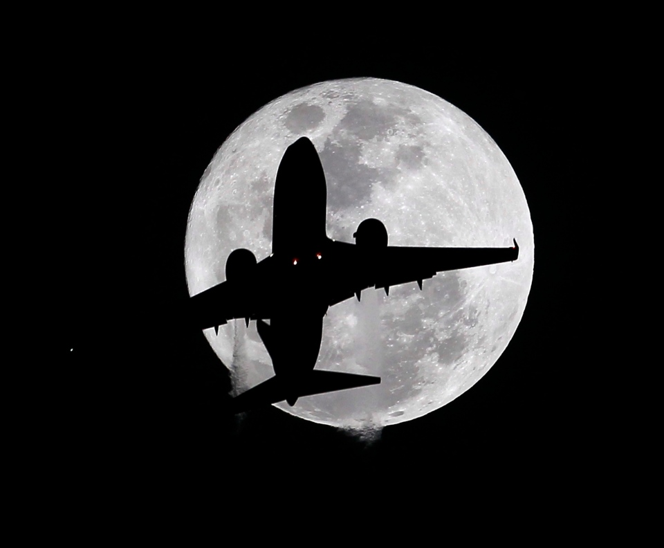 A passenger plane crosses the full moon as it passes on its way to the Los Angeles International Airport in Whittier, Tuesday, Feb. 3, 2015. (Nick Ut/AP Photo)