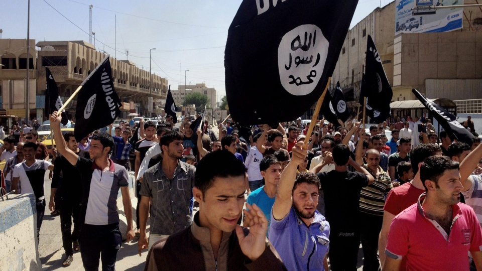Demonstrators chant pro-Islamic State group, slogans as they carry the group's flags in front of the provincial government headquarters in Mosul, 225 miles (360 kilometers) northwest of Baghdad, June 16, 2014. (AP Photo, File)