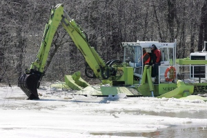 Crews operate an Amphibex as it breaks up ice on the Red River in Winnipeg on Thursday, April 9, 2009. (John Woods / THE CANADIAN PRESS)