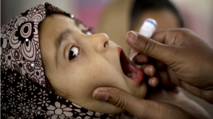 A Pakistani health worker gives polio vaccine to a child at a bus terminal in Rawalpindi, Pakistan on Feb. 16, 2015. (AP / B.K. Bangash)