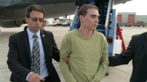 Luka Rocco Magnotta is taken by police from a Canadian military plane to a waiting van in Mirabel, Que. on on June 18, 2012. (THE CANADIAN PRESS)