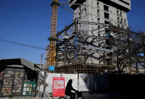 A cyclist rides past a closed newsstand and a construction site on the Lunar New Year's Eve in Beijing, China Wednesday, Feb. 18, 2015. (AP Photo/Andy Wong)