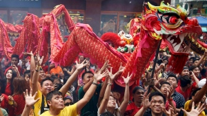Filipinos try to catch sweets and giveaways being thrown at them following dragon and lion dance performances in front of a supermarket at Manila's Chinatown district of Binondo to celebrate the Chinese New Year Thursday, Feb. 19, 2015 in Manila, Philippines. (AP / Bullit Marquez)