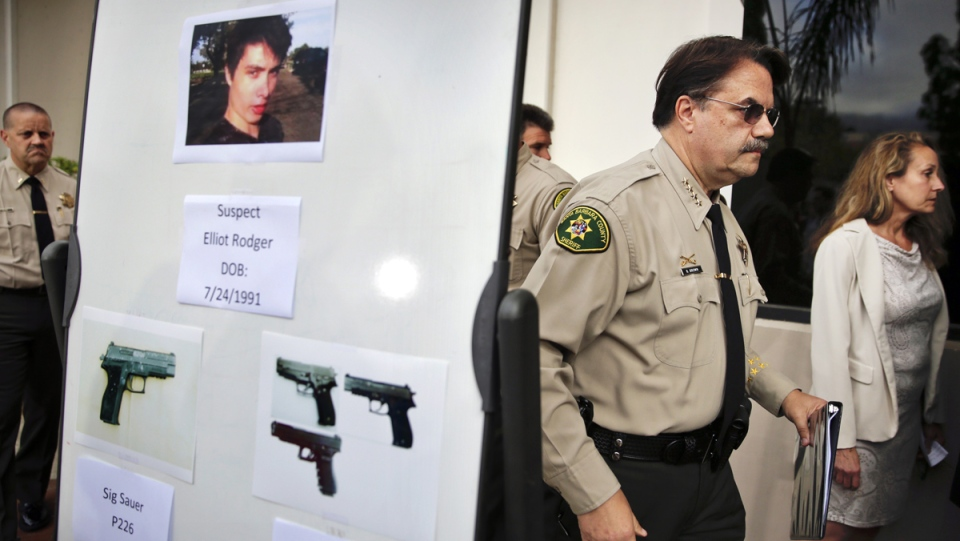 Santa Barbara County Sheriff Bill Brown, right, walks past a board showing the photos of gunman Elliot Rodger and the weapons he used in the mass shooting that took place in Isla Vista, Calif., after a news conference in Santa Barbara, Calif., May 24, 2014. (AP / Jae C. Hong)