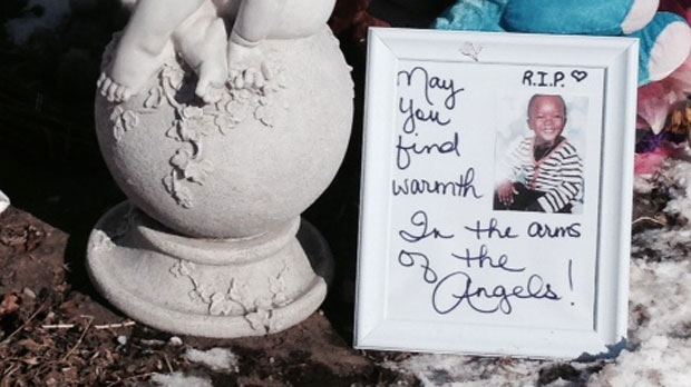 At a memorial for three-year-old Elijah Marsh in Toronto, a frame holding a picture of toddler reads, 'May you find warmth in the arms of the angels.' (Cam Woolley/ CP24)