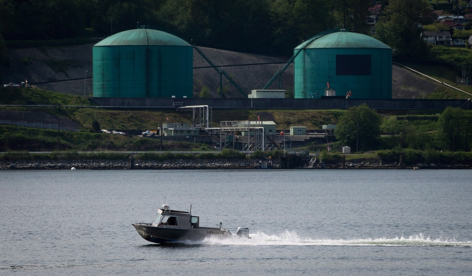 A fishing boat in North Vancouver passes the Kinder Morgan Burnaby Terminal in Burnaby, B.C., on May 2, 2014. (Darryl Dyck / THE CANADIAN PRESS)
