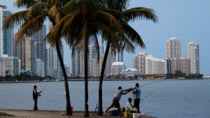 In this file photo, people fish under the William Powell bridge at sunset with the skyline of Miami in the background, Tuesday, Aug. 21, 2012. AP Photo/Lynne Sladky)
