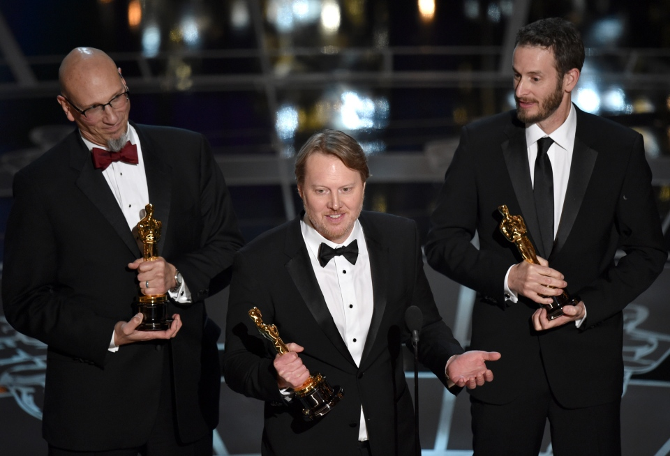 Roy Conli, from left, Don Hall, and Chris Williams accept the award for best animated feature film for 'Big Hero 6' at the Oscars on Sunday, Feb. 22, 2015, at the Dolby Theatre in Los Angeles. (Photo by John Shearer/Invision/AP)