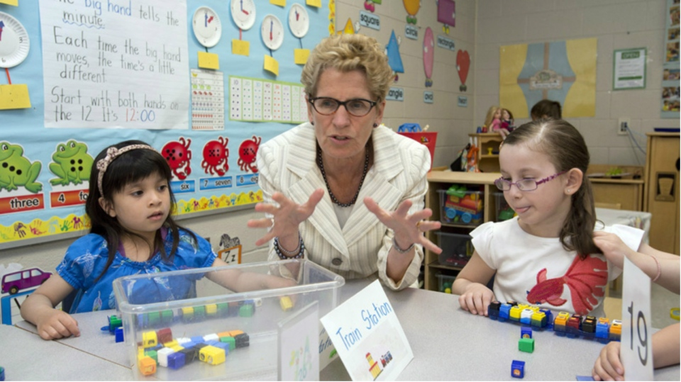 Premier Kathleen Wynne sits with school children in Markham, Ont., on May 28, 2014 (Frank Gunn / THE CANADIAN PRESS)