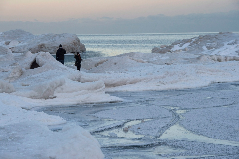 A couple take photos while standing on ice blown ashore in east-end Toronto on Monday, Feb. 16, 2015. (Frank Gunn / THE CANADIAN PRESS)
