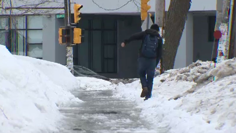 A pedestrian attempts to navigate an icy sidewalk in Halifax on Feb. 23, 2015.