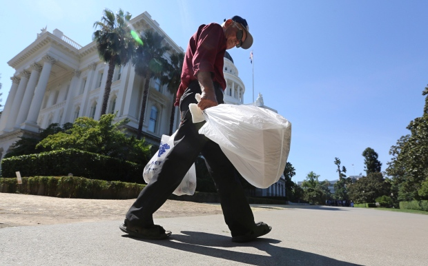 Shopper carries single-use plastic bags