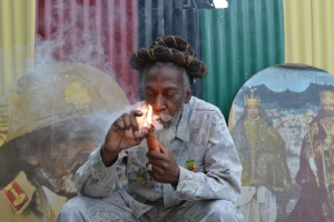 """In this Aug. 28, 2014 file photo, legalization advocate and reggae legend Bunny Wailer smokes a pipe stuffed with marijuana during a """"reasoning"""" session in a yard in Kingston, Jamaica. (AP / David McFadden, File)"""