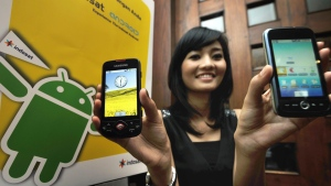A model displays smartphones with Google's mobile operating system Android. (AFP PHOTO / Bay ISMOYO)
