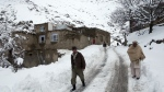 Afghan men walk in a village close to an avalanche site in Panjshir province north of Kabul, Afghanistan, Wednesday, Feb. 25, 2015. (AP / Massoud Hossaini)