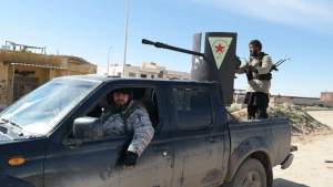In this Feb. 24, 2015 image posted on a militant social media account by the Al-Baraka division of the Islamic State group, Islamic State militants ride in a Kurdish vehicle captured during fighting in Tal Tamr, Hassakeh province, Syria.