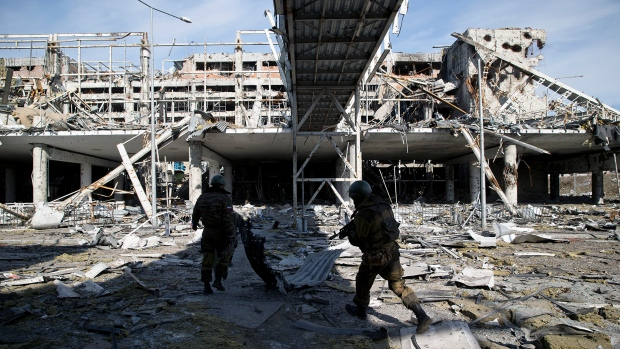 Russia-backed rebels walk near the destroyed building of the airport outside Donetsk, Ukraine, Wednesday, Feb. 25, 2015. <br> <br> Once a showpiece for Ukraine, the Donetsk International Airport is now a bitter battleground and a grim work site for Ukrainian prisoners of war. (AP / Vadim Ghirda)