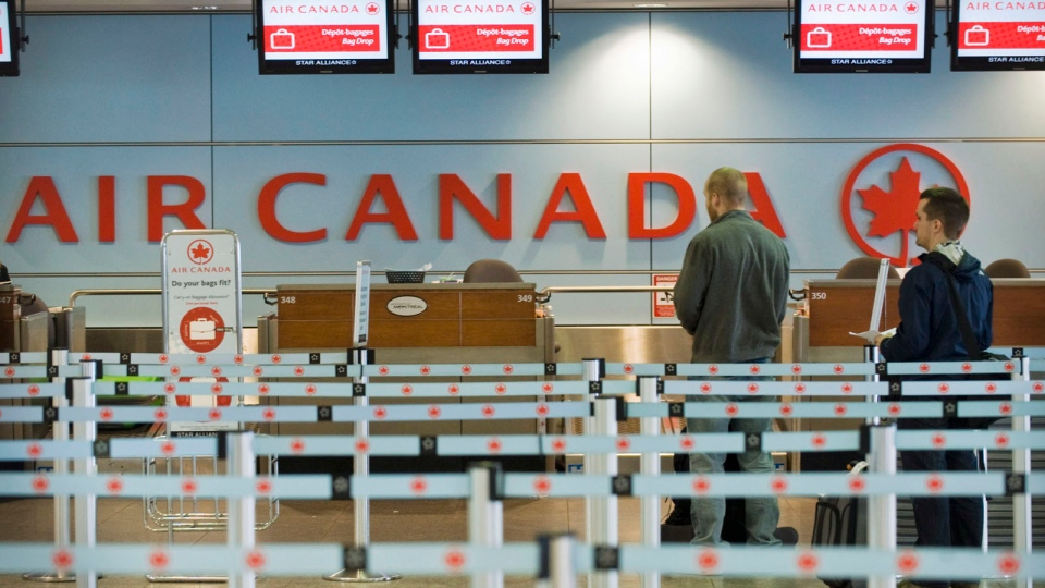 Air Canada passengers queue at Trudeau Airport in Montreal, on Friday, Apr. 13, 2012. (Graham Hughes/The Canadian Press)