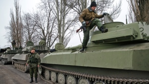 Russia-backed separatist fighters stand on self propelled 152 mm artillery pieces, part of a unit moved away from the front lines, in Yelenovka, near Donetsk, Ukraine,Thursday, Feb. 26, 2015. (AP / Vadim Ghirda)