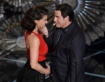 In this Feb. 22, 2015 file photo, John Travolta, right, touches the face of Idina Menzel as they present the award for best original song at the Oscars at the Dolby Theatre in Los Angeles. (Photo by John Shearer/Invision/AP, File)