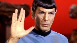 Spock gives a Vulcan salute, used in greetings and farewells. The formal phrase associated with the salute is 'Live long and prosper.'