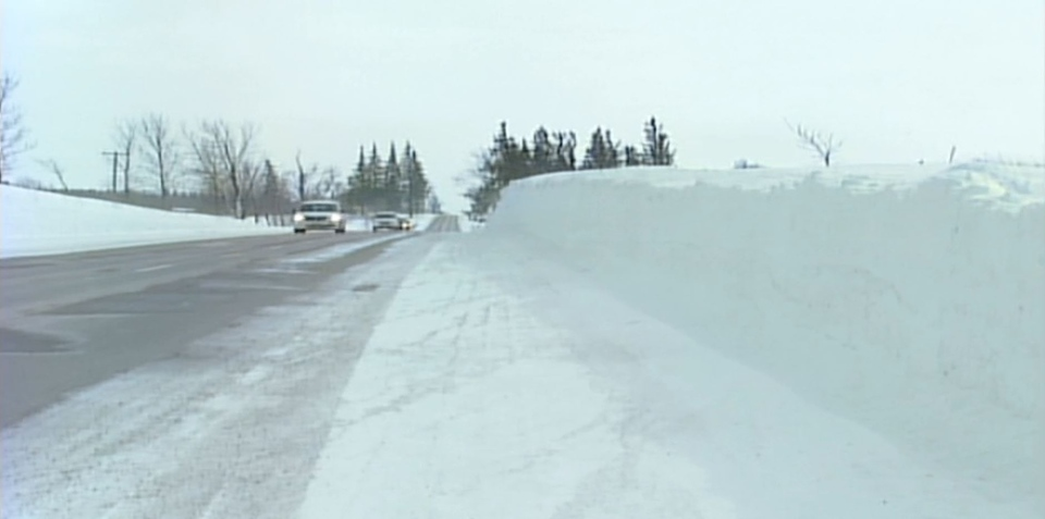 Vehicles are dwarfed by giant snow banks in Bruce County, Ont. on Thursday, Feb. 26, 2015. (Scott Miller / CTV London)