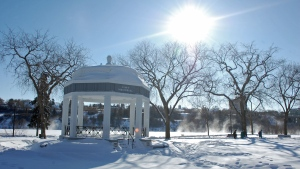 The Vimy Memorial Bandshell sits in Saskatoon's Kiwanis Park on a cold February 2015 day. Steam can be seen rising from the river as a group walks through the park.
