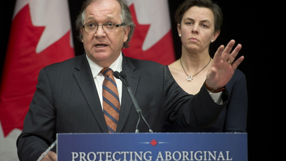Minister of Aboriginal Affairs and Northern Development Bernard Valcourt responds to a question as Labour Minister Kellie Leitch looks on during a news conference following the National Roundtable on Missing and Murdered Indigenous Women and Girls, in Ottawa, Friday, Feb. 27, 2015. (Adrian Wyld / THE CANADIAN PRESS)