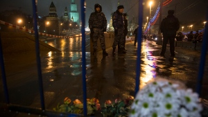 Flowers lie on the ground as Russian police officers stand near the place where Boris Nemtsov, a former Russian deputy prime minister and opposition leader, was kiiled at Red Square with the Kremlin Wall in the background in Moscow, Russia, Saturday, Feb. 28, 2015. (AP / Pavel Golovkin)