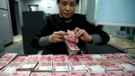 In this Jan. 22, 2015 photo, a clerk counts Chinese currency notes at a bank branch in Huaibei in central China's Anhui province. (AP Photo)