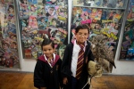 Harry Potter fans Mateo Lara, 5, right, and his brother Francisco, 7, pose for photos with a live owl inside an exhibition of Harry Potter memorabilia, at the Mexican Museum of Antique Toys, in Mexico City on Friday, Feb. 27, 2015. (AP / Rebecca Blackwell)