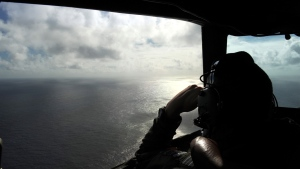 In this April 13, 2014 file photo taken from the Royal New Zealand air force (RNZAF) P-3K2-Orion aircraft, pilot and aircraft captain, Flight Lt. Timothy McAlevey looks out of a window while searching for debris from missing Malaysia Airlines Flight 370, over the Indian Ocean off the coast of western Australia. (AP / Greg Wood, Pool, File)