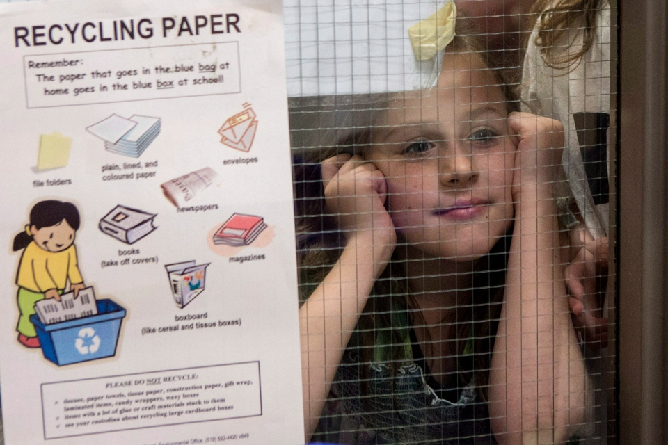 Isabella Schiavone a grade 3 student at Westwood Public School in Guelph, Ontario peers through a glass panel at on Wednesday May 14 , 2014. (Chris Young/THE CANADIAN PRESS)