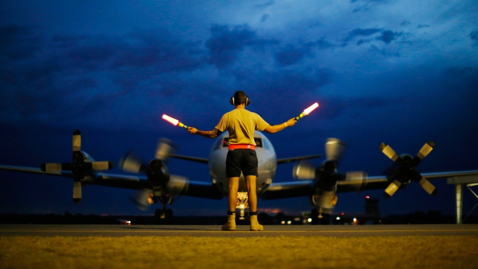 A ground controller guides a Royal Australian Air Force AP-3C Orion to rest after sunset upon its return from a search for the missing Malaysia Airlines flight MH370 over the Indian Ocean, at the Royal Australian Air Force base Pearce in Perth, Monday, March 24, 2014. (AP / Jason Reed)