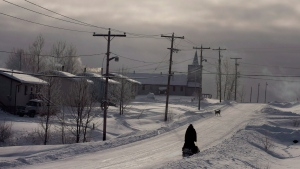 A snowmobile rides down the main street Tuesday, December 18, 2012, on the Fort Hope First Nation, Ont. (Ryan Remiorz /The Canadian Press)