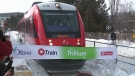 A new train on Ottawa's Trillium Line breaks a ribbon as it arrives at a stop this morning.
