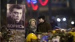 A couple comes to pay respects at the place where Boris Nemtsov, a charismatic Russian opposition leader and sharp critic of President Vladimir Putin, was gunned down on Friday, Feb. 27, 2015 near the Kremlin, in Moscow, Russia, on March 2, 2015. (AP / Alexander Zemlianichenko)