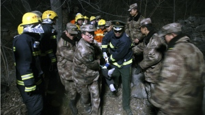 Rescuers carry an injured person from a bus accident site in Linzhou in central China's Henan province on March 3, 2015. (AP)