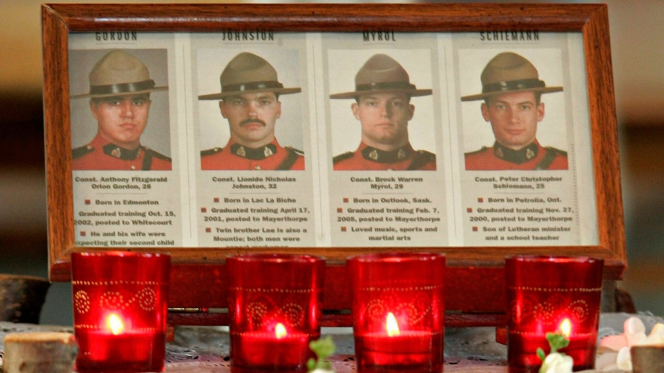 Four candles burn beside the images of the four RCMP officers killed at a memorial service on the Alexis reserve 30km east of Mayerthorpe, Alta, Sunday March 6, 2005. (Adrian Wyld / The Canadian Press)