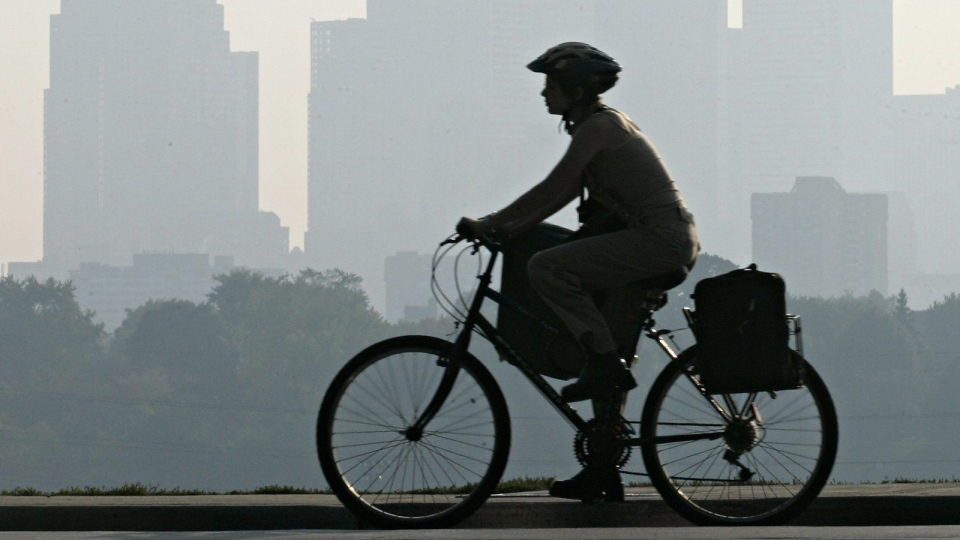 A woman cycles past the downtown Toronto skyline as smog hangs over the city on Tuesday, Oct. 4, 2005. (THE CANADIAN PRESS/Adrian Wyld)