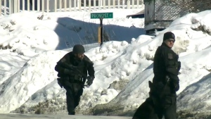 Tactical officers surround a home as part of an investigation into potential threats to a nearby mall, in Dartmouth, N.S., Tuesday, Feb. 3, 2015.