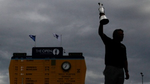 A silhouetted Darren Clarke holds up the Claret Jug trophy at the British Open Golf Championship at Royal St George's golf course, on July 17, 2011. (AP / Matt Dunham)