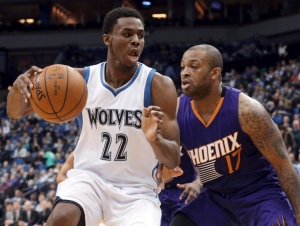 Minnesota Timberwolves' Andrew Wiggins, left, drives around Phoenix Suns' P.J. Tucker during the second half of an NBA basketball game on Feb. 20, 2015, in Minneapolis. (Jim Mone / AP Photo)