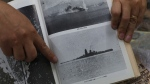 Historian Professor Rico Jose shows a picture taken before the Japanese battleship Musashi sank. (AP / Aaron Favila)