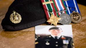 A photo of Cpl. Stuart Langridge is seen along with his beret and medals at a news conference on Parliament Hill in Ottawa, Thursday, Oct. 28, 2010. (Adrian Wyld / THE CANADIAN PRESS)