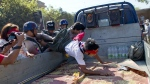 Police officers push student protesters onto the back of a truck in Letpadan, north of Yangon, Myanmar on March 6, 2015. (AP / Gemunu Amarasinghe)