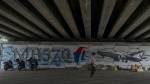A man walks past MH370 related street art under a flyover in Kuala Lumpur, Malaysia on March 6, 2015. (AP / Joshua Paul)