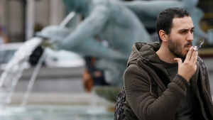A man smokes by the fountains in Trafalgar Square in London, on Wednesday, Oct. 15, 2014. (AP Photo/Kirsty Wigglesworth)